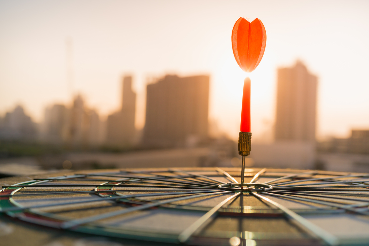 Red dart arrow hitting in the target center of dartboard with modern city and sunset background. Target business, achieve and victory concept .